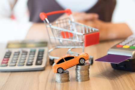 Concept Of Buying New Car By Money With Red Shopping Cart