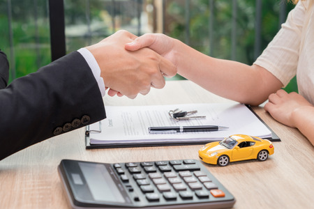 Sale man or businessman shaking hands with female after car loan agreement was signed. Zdjęcie Seryjne