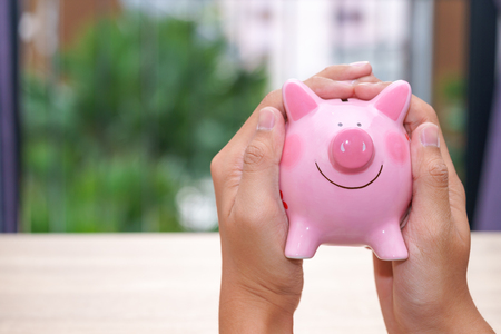 Hand holding pink piggy bank on wooden desk - save money concept Stock Photo