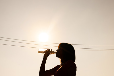 Female drinking water in hot summer - heat stroke concept Stock Photo