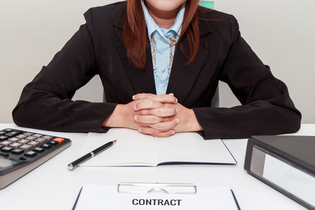 statute: Businesswoman holding her own hands while sitting at desk - signing contract concept Stock Photo