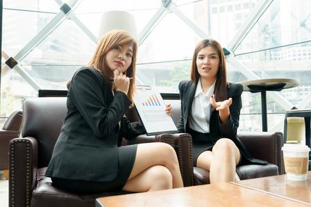 Geschäftsfrau zwei, die über ihre Arbeit - Geschäftstreffenkonzept spricht und denkt Standard-Bild