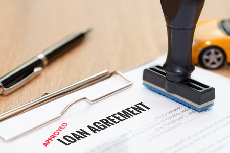 lend: Approved loan agreement document with rubber stamp and car model toy on wooden desk
