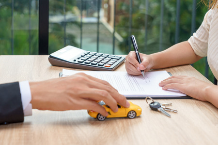 Woman signing car loan agreement contract with car key and calculator on wooden desk Stock Photo
