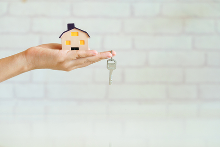 Real estate agent hand holding house and house key