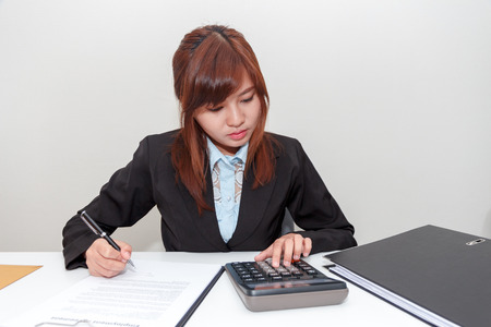 Businesswoman pushing calculator with notebook and pen on desk - working concept