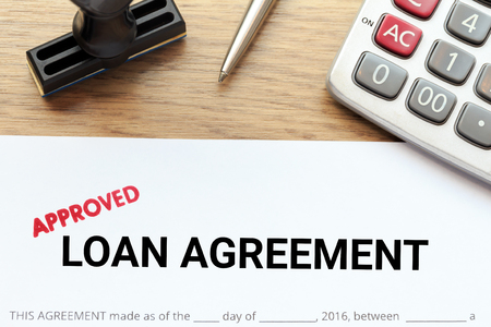 Approved loan agreement document with rubber stamp and calculator on wooden desk Stock Photo