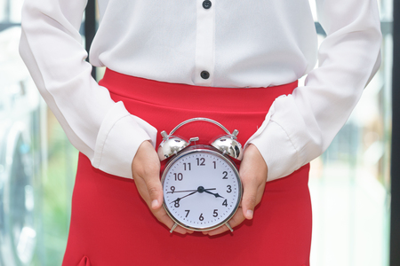Woman holding alarm clock with red skirt - woman on her period