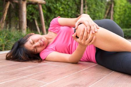Femme asiatique qui touche son genou blessé à l'extérieur - concept de douleur Banque d'images
