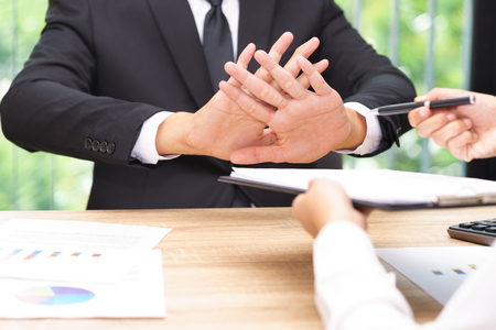 Businessman says no or hold on when businesswoman giving pen for signing a contract. 写真素材