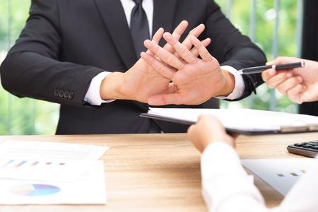 Geschäftsmann sagt nein oder hält an, wenn Geschäftsfrau Stift für das Unterzeichnen eines Vertrages gibt.