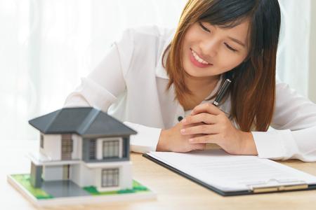 Sonrisa mujer mirando a su casa y preparándose para firmar un contrato de inversión - satisfacer en casa Foto de archivo