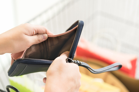 Close up of woman hands holding an empty wallet over shopping bags Reklamní fotografie