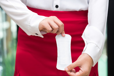 Woman holding sanitary napkins with red skirt - woman on her period
