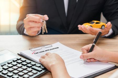 Uomo d'affari che dà la chiave dell'automobile e contratto di prestito di firma del cliente con il calcolatore sullo scrittorio di legno Archivio Fotografico - 90341298