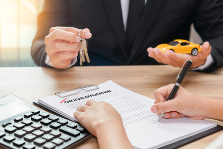 Businessman giving car key and customer signing loan agreement with calculator on wooden desk