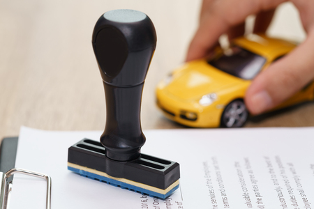 Approved rubber stamp and car model toy with loan application on wooden desk Stock Photo