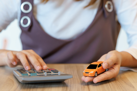 Woman calculating money with car insurance concept and calculator
