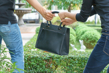 Thief stealing and jerking handbag from woman at public park Archivio Fotografico