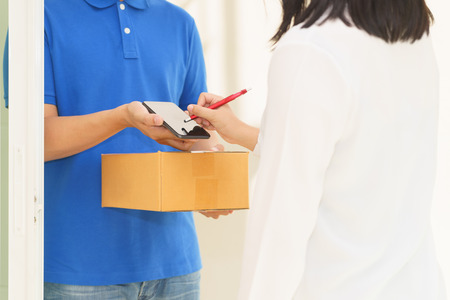 Woman receiving package and signing on digital mobile phone from delivery man