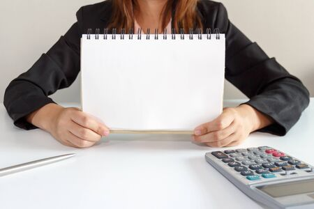 Business woman in black suit showing blank page of note pad on desk.
