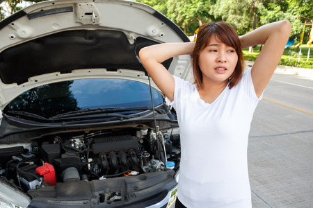 Closeup portrait, Stressed woman looking for someone help with opening car hood - car breakdown. Stock Photo