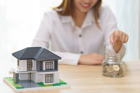 Woman hand putting a coin into a jar bank on wooden desk - save money to buy new house concept