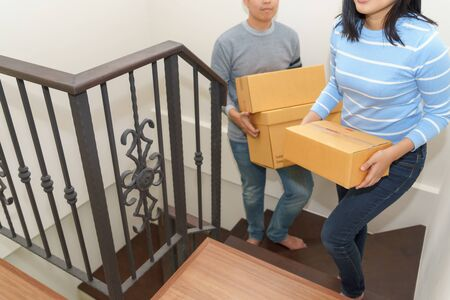 Couple holding boxes and walking up stair - moving house concept.