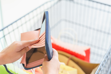 Close up of woman hands holding an empty wallet over shopping bags Stock Photo