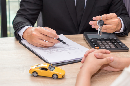 Businessman giving car key and explain about loan agreement with car model on wooden desk. Stock Photo