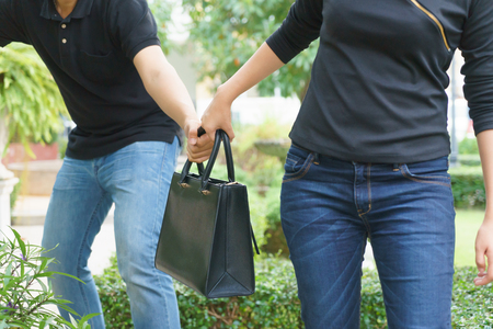Thief stealing and jerking handbag from woman at public park. Stock Photo