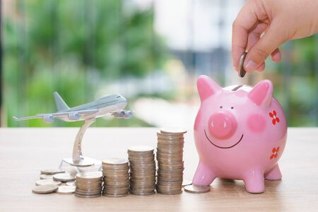Holiday saving money with piggy bank and plane model - Stacking coins for traveling concept Stock Photo