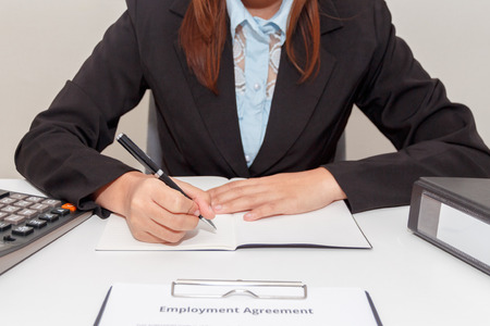 Hands of businesswoman writing on notebook with calculator and employment agreement at desk.