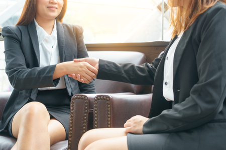 Close up of two smile businesswoman shaking hands while sitting in room concept.