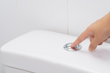 Close up of finger pushing a flush toilet button for cleaning. - save water concept.