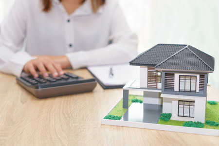 Woman calculating about installment price with estate loan agreement document and home model Stock Photo