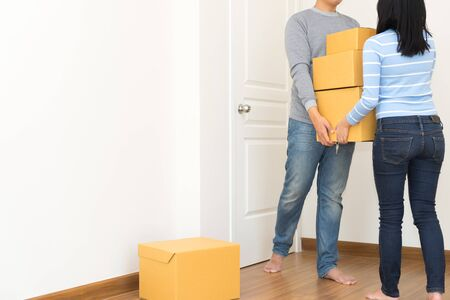 Couple holding boxes and walking together - moving house concept. Stock Photo