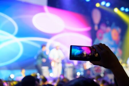 Hand with smartphone recording live music festival, Taking photo of concert stage