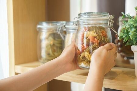 Hands picking macaroni in glass jar for preparing food