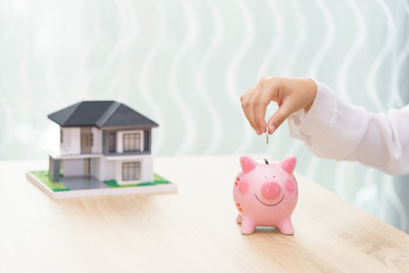 Woman hand putting a coin into a piggy bank on wooden desk - save money to buy new house concept