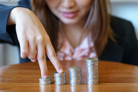 Fingers of businesswoman walking on coins with wooden desk.