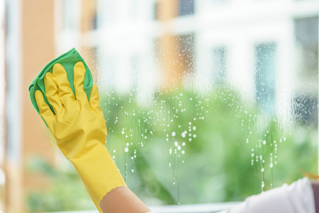 Woman housekeeper cleaning the mirror with green cloth. Reklamní fotografie - 94430100