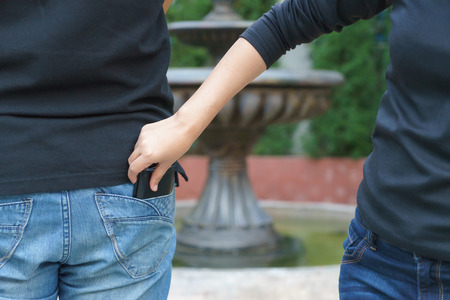 Female pickpocket stealing a wallet from behind pocket on jeans at park.