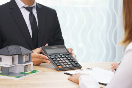 Businessman showing the home price on calculator and customer ready to sign loan contract Stock Photo