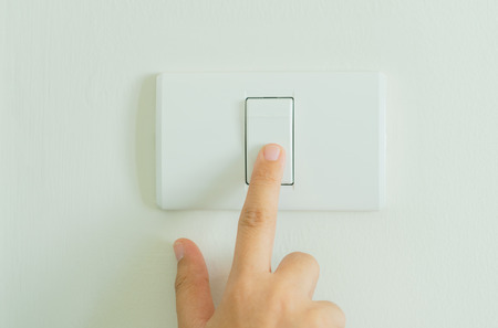 Close up of finger turning off on light switch on wall