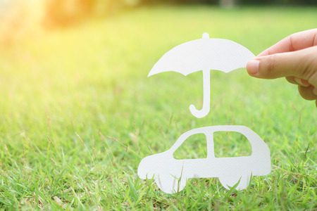 Paper car and umbrella on green field with sunlight - car insurance concept