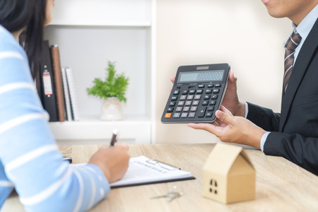 Businessman showing the home price on calculator and customer ready to sign loan contract Foto de archivo