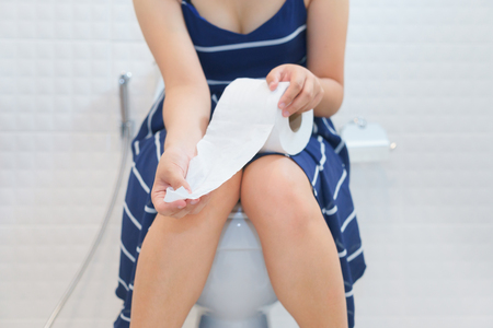 Woman sitting on toilet with toilet paper - constipation concept