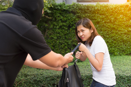 Thief stealing and jerking handbag from young woman at public park with fair. Stock Photo