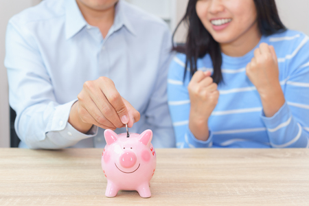 Smile couple putting a coin into a pink piggy bank on wooden desk - save money for the future